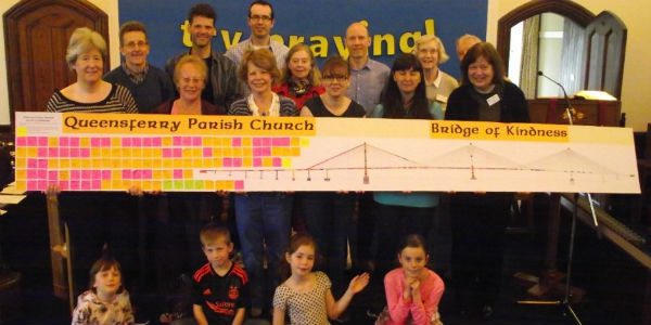 Group holding image of the Bridge of Kindness
